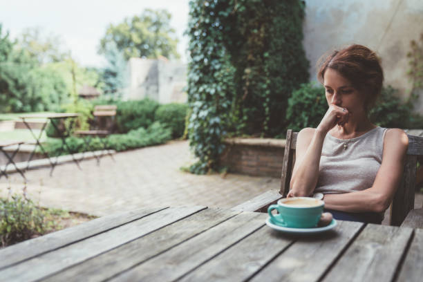 Depressed woman drinking coffee at the veranda Unhappy woman sitting thoughtfully at the back yard relationship difficulties stock pictures, royalty-free photos & images