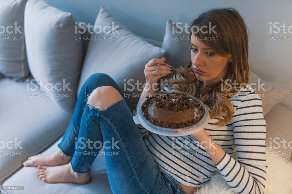 Deprimida mujer come torta - foto de stock