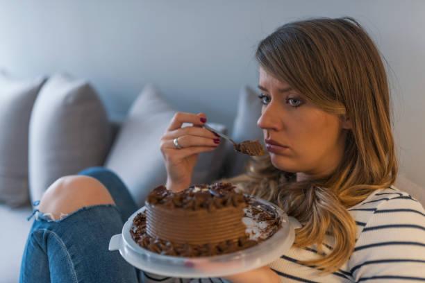 depressed woman eats cake - niezdrowe jedzenie zdjęcia i obrazy z banku zdjęć