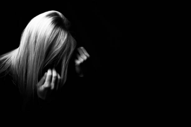 depressed woman hiding her face in a dark - domestic violence stock pictures, royalty-free photos & images