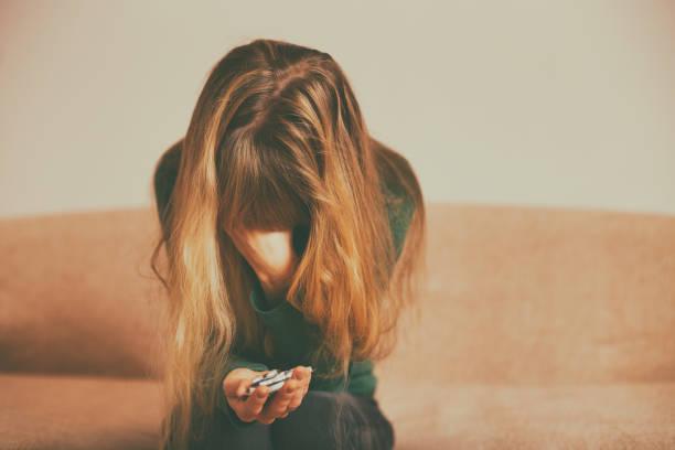Depressive Frau hält Tabletten – Foto