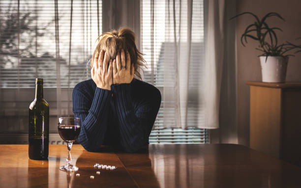 Depressed woman is drinking red wine and taking pills at home alone stock photo