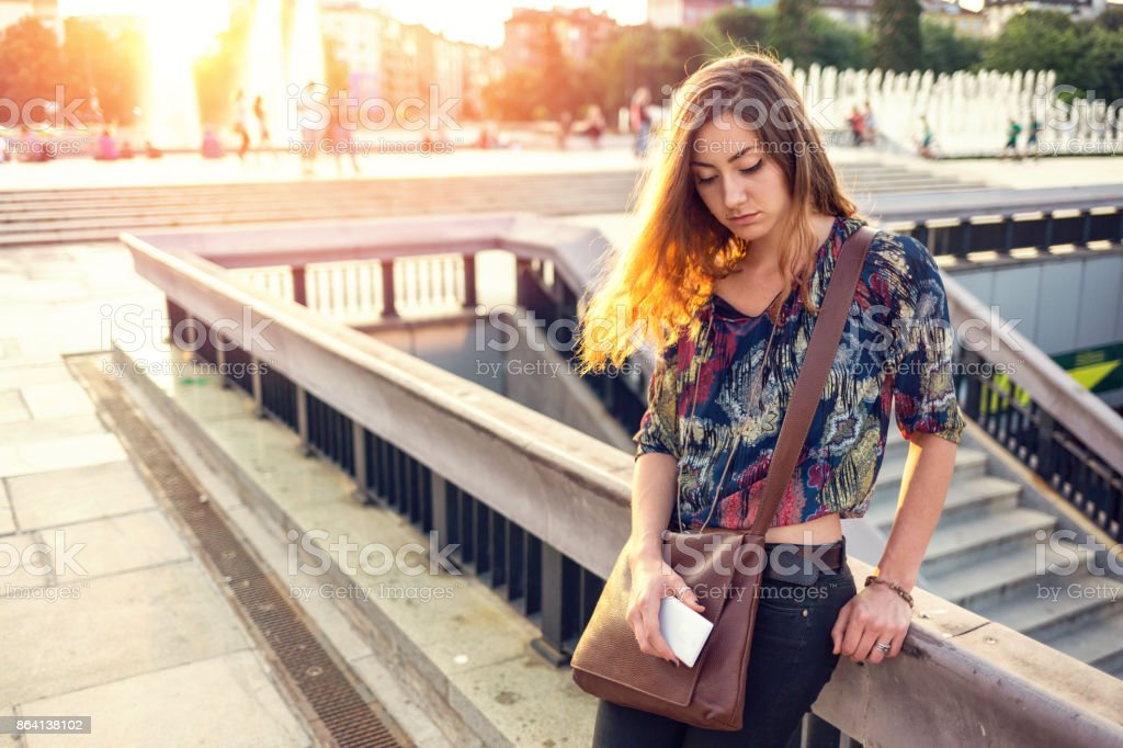Depressed woman leaning on the footbridge and browsing on her laptop royalty-free stock photo