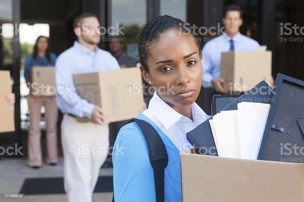 Depressed woman leaving office after being fired or laid off stock photo