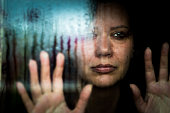 istock Depressed woman looking out of rainy window 1223140462