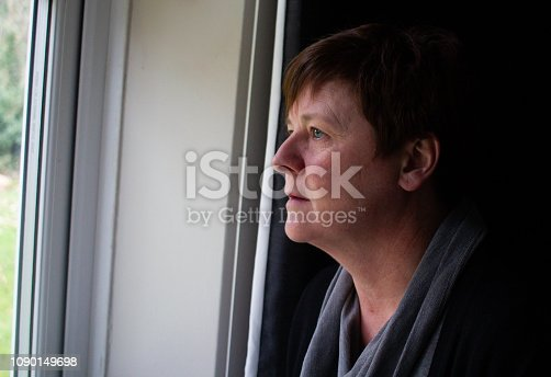 543048812 istock photo Depressed Woman Looking Out of the Window. 1090149698
