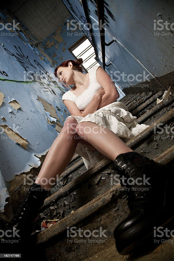 Depressed Woman on Stairs in Abandoned Building royalty-free stock photo