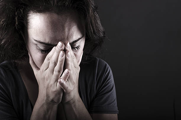Depressed woman Depressed woman with hands over her face. Crying. mourner stock pictures, royalty-free photos & images