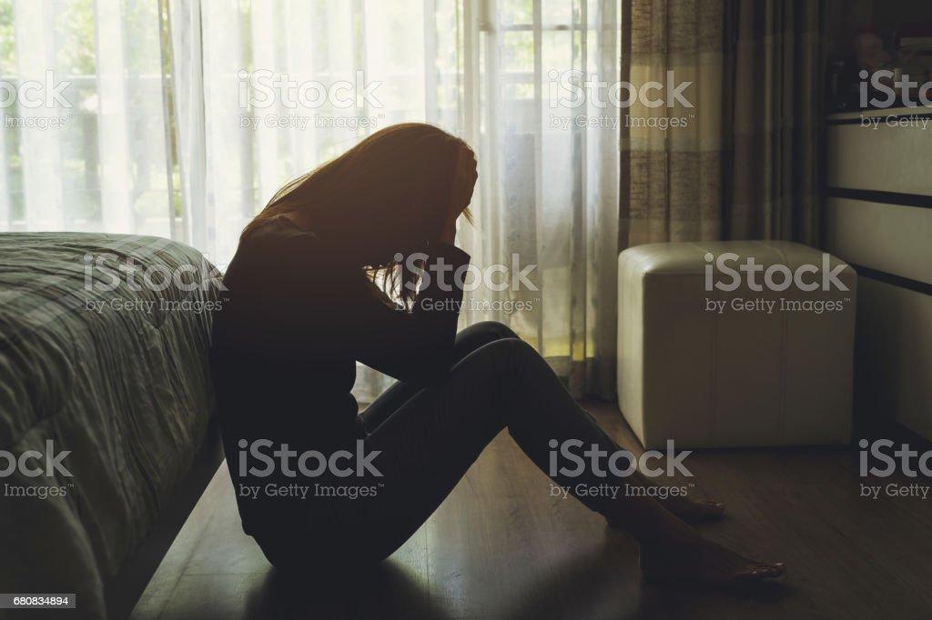 暗い寝室に座っている落ち込んだ女性 - ストレスのロイヤリティフリーストックフォト