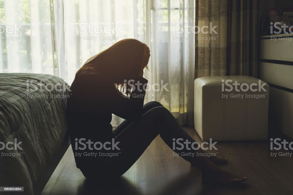 depressed woman sitting in the dark bedroom stock photo