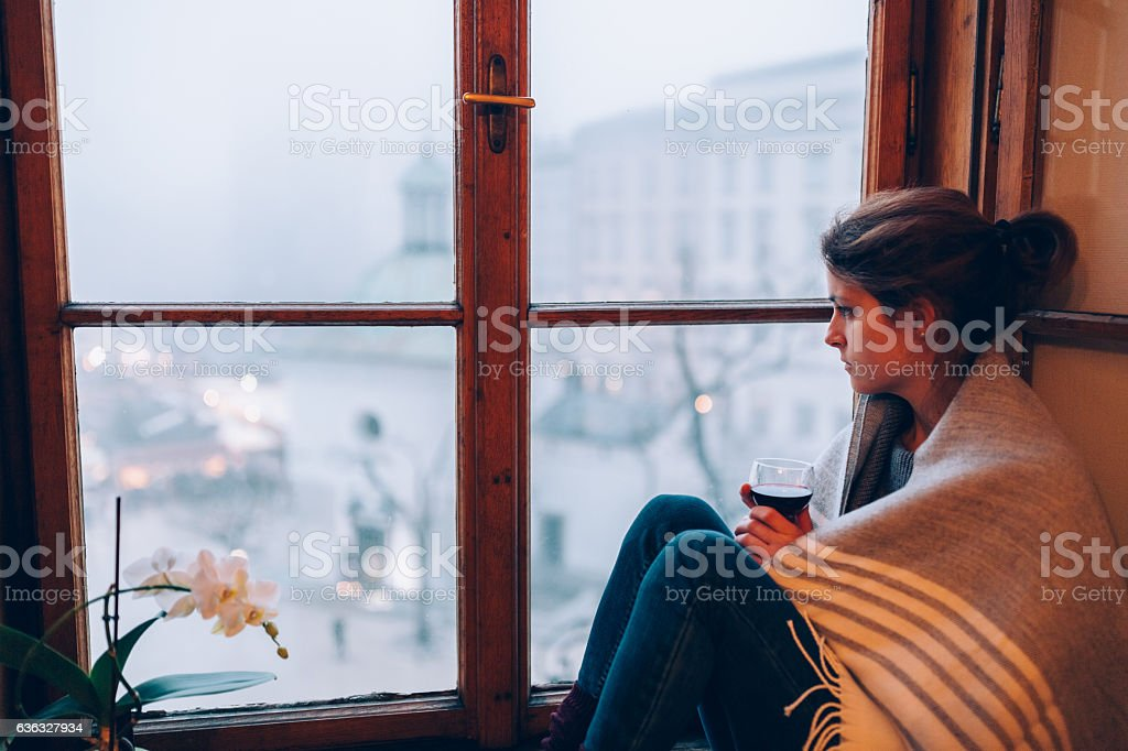 Depressed woman sitting near the window stock photo