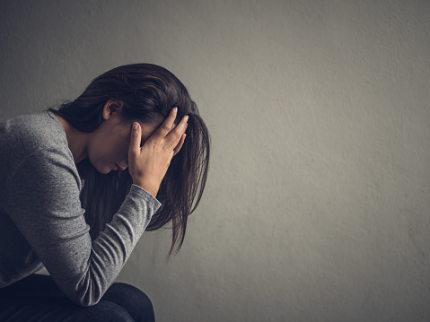 istock Depressed woman sitting on a chair in dark room at home. Lonly , sad, emotion concept. 865618914