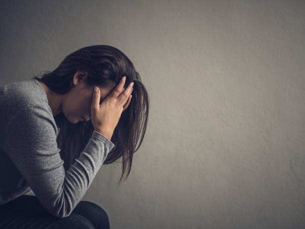 donna depressa seduta su una sedia in una stanza buia a casa. lonly , triste, concetto di emozione. - assuefazione foto e immagini stock