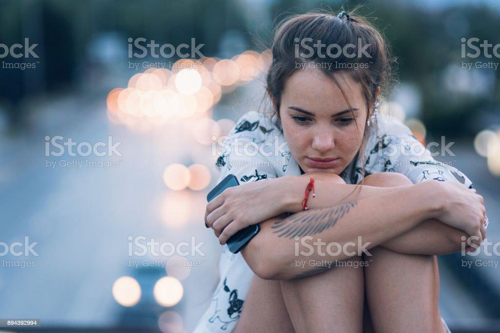 Depressed woman sitting on the bridge parapet stock photo