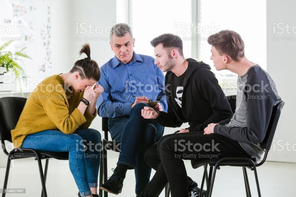 Depressed woman sitting with friends and therapist Depressed woman sitting with friends and social worker in lecture hall. Mental therapist is with young students during meeting in university. They are in group therapy session. 18-19 Years Stock Photo