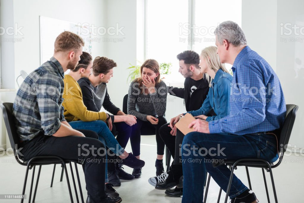 Depressed woman sitting with friends and therapist Social worker and friends looking at crying depressed woman. Mental health therapist is with young students during meeting in university. They are in group therapy session. 18-19 Years Stock Photo