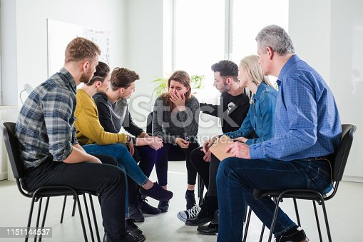 956725746 istock photo Depressed woman sitting with friends and therapist 1151144537