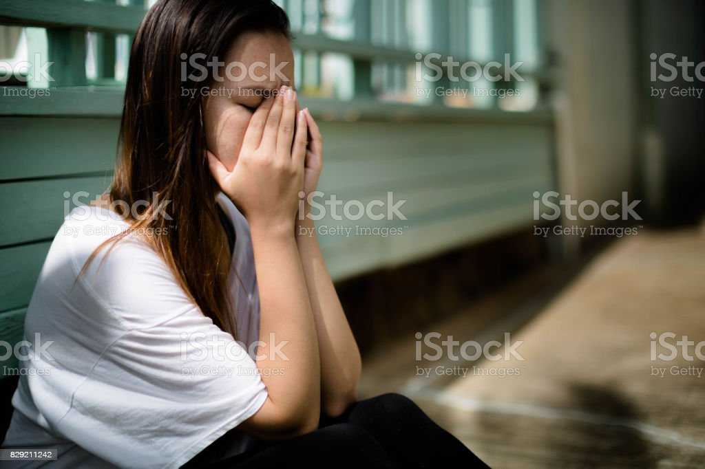 Depressed woman sitting with her hands covering her face overwhelmed with emotion stock photo