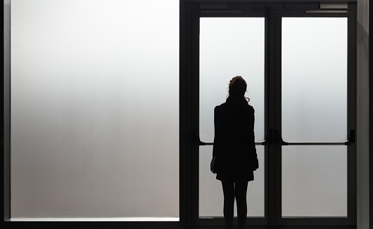 istock Depressed woman waiting in front a glass door in a white room ready to react - Disease - Abuse - phobia Concept 912134542