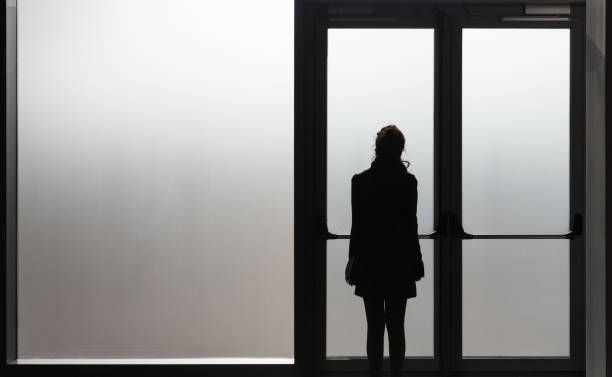 Depressed woman waiting in front a glass door in a white room ready to react - Disease - Abuse - phobia Concept stock photo
