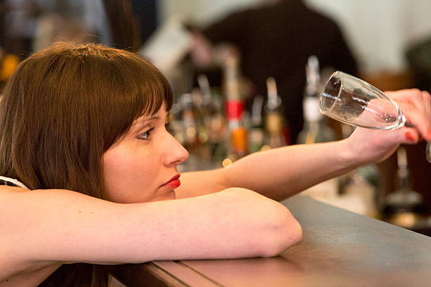 Depressed Woman with empty glass stock photo