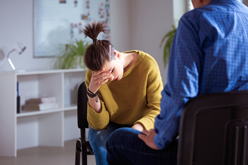 Depressed Woman With Head In Hand At Therapy Stock Photo - Download Image Now