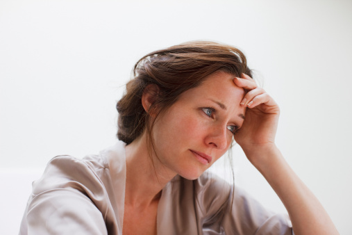 istock Depressed woman with head in hands 107429862