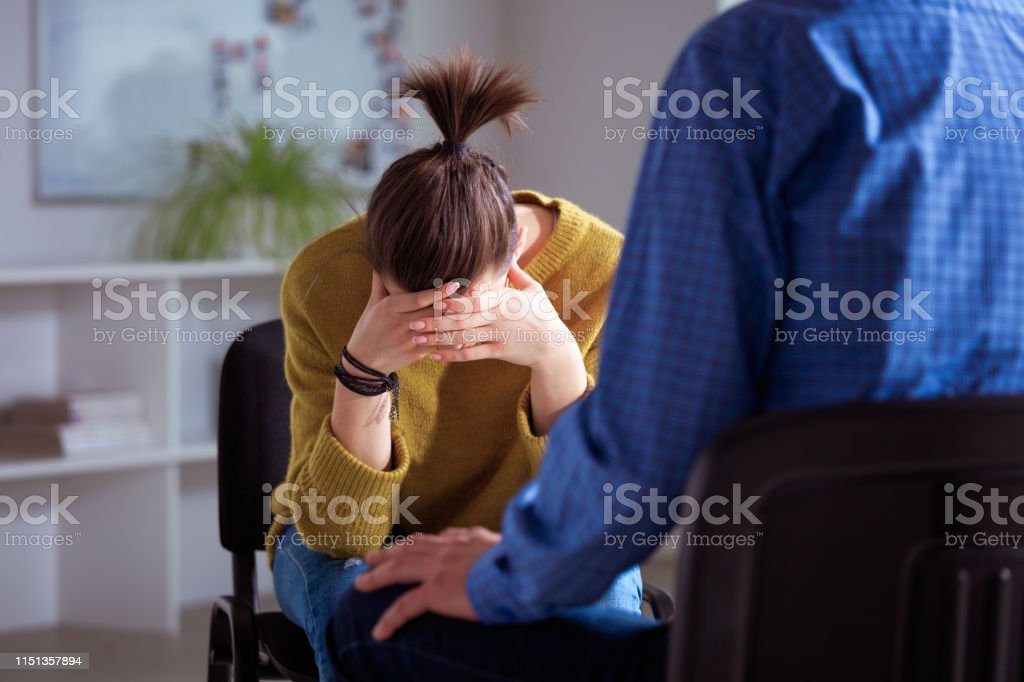 Depressed woman with therapist in university Depressed student with head in hand having discussion in lecture hall. Social worker is solving female's problems. They are in therapy at university. 18-19 Years Stock Photo