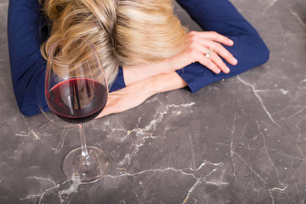 Depressed woman with wine glass resting her head on counter stock photo