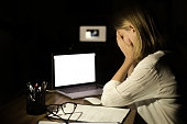 Depressed woman working with computer at night