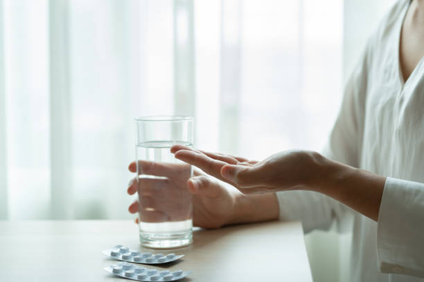 depressed women hand hold medicine with a glass of water, healthcare and medicine recovery concept depressed women hand hold medicine with a glass of water, healthcare and medicine recovery concept abortion stock pictures, royalty-free photos & images
