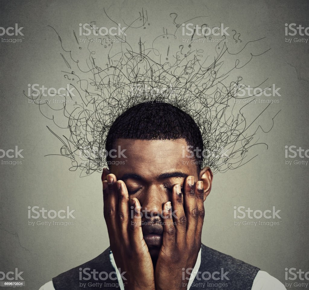 Depressed worried young man with worried desperate stressed expression hands covering face and brain melting into lines question marks – zdjęcie