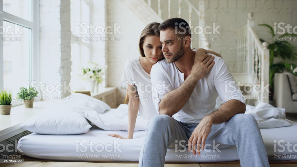 Depressed yong man sitting in bed having stressed while his girlfriend come and embrace him and kiss in bedroom at home stock photo