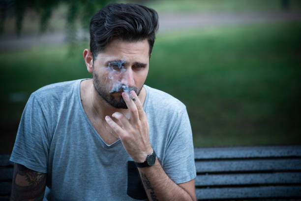 Depressed young adult man sitting on a bench smoking a cigarette - foto stock