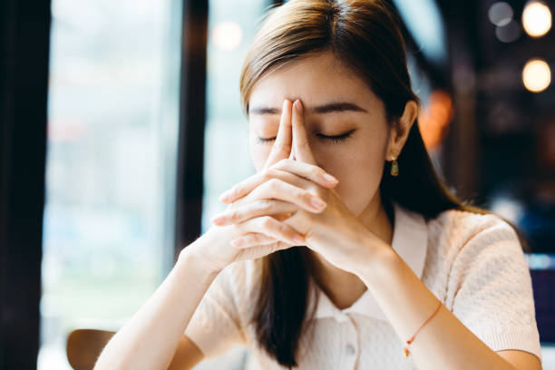 Depressed young Asian woman having headache while drinking coffee at cafe. stock photo