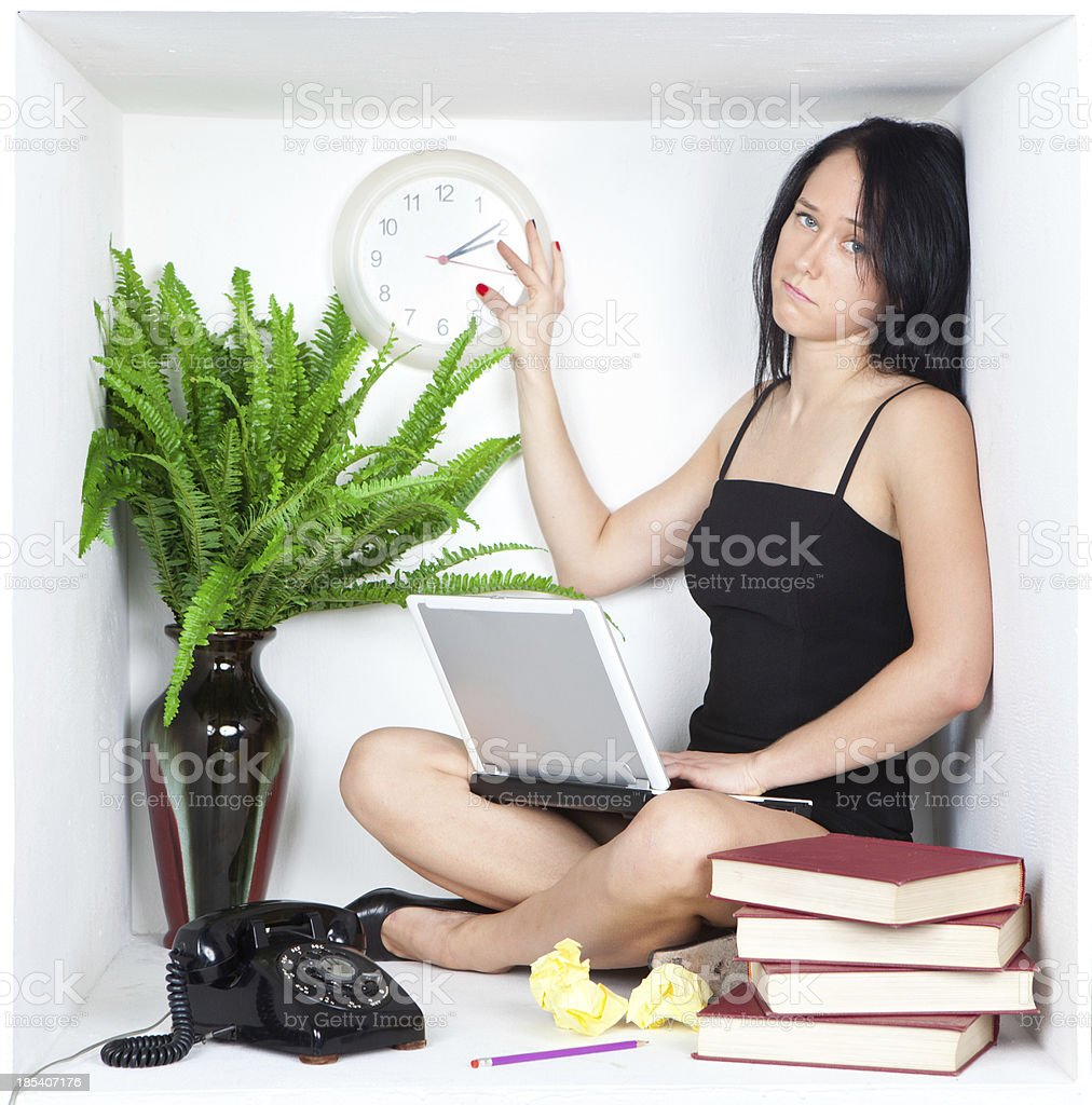 Depressed young business woman in a small office cubicle stock photo