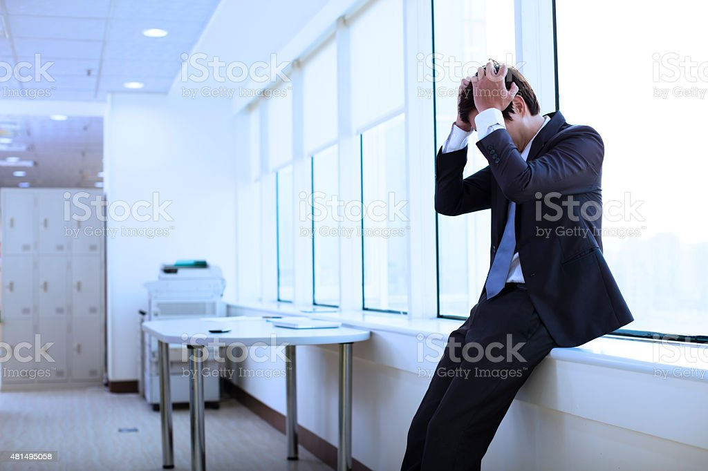 Depressed young businessman in office stock photo