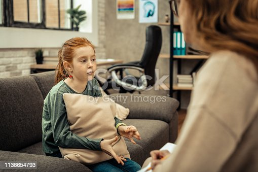 istock Depressed young girl having a session with psychologist 1136654793