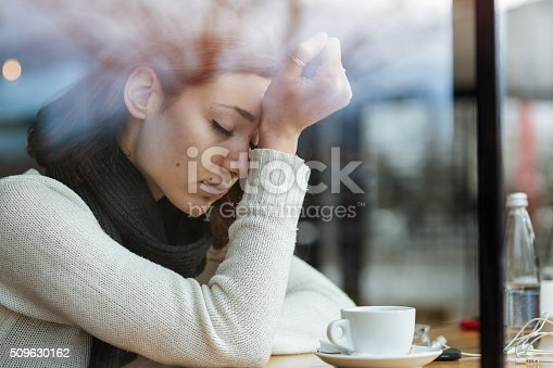 Young girl smoking and feeling depressed in a bar
