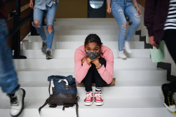Depressed young student with face mask sitting on floor back at college or university, coronavirus concept. stock photo