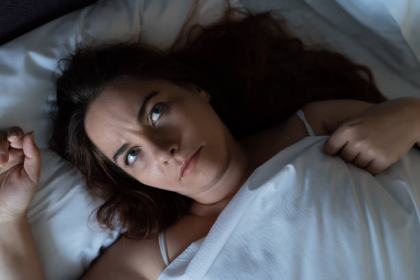 depressed young woman dont sleep at night, lying on bed, looks up and suffers from insomnia, top view - dont sleep stock pictures, royalty-free photos & images