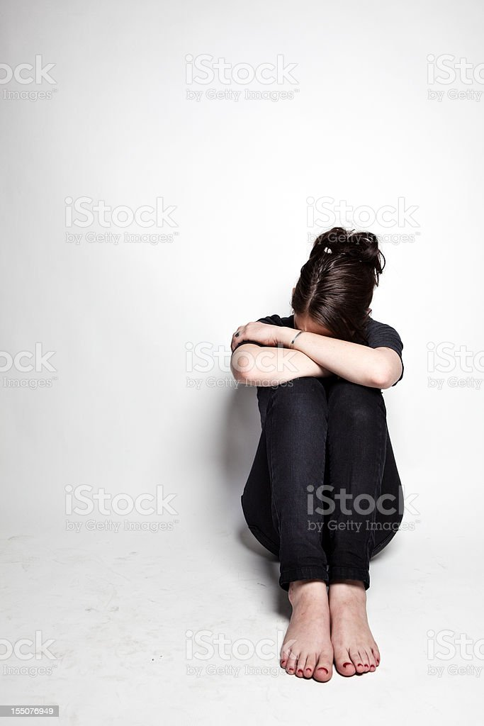 Depressed young woman in black sits, hiding face royalty-free stock photo