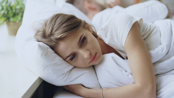Depressed young woman lying in bed and feeeling upset after quarrel with her boylfriend in bed at home stock photo