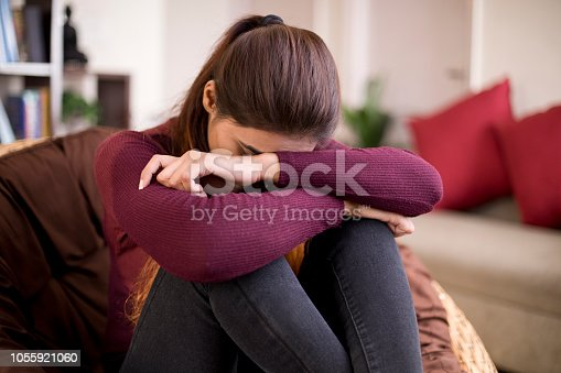 Worried young woman sitting at home with her head down