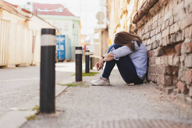 Depressed young woman sitting down with her head on her knees stock photo