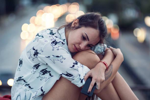 Depressed young woman sitting on the bridge parapet stock photo