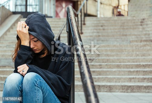 Teenage girl sitting outdoors on the staircase covering her head with sweatshirt hood