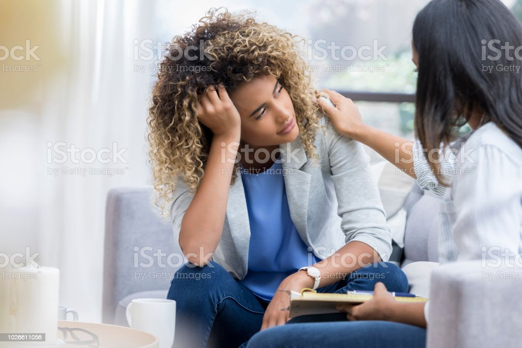 Depressed young woman talks to therapist A young woman sits on a couch with her unrecognizable therapist.  She puts her head in her hand as she looks out the window with a sad expression.  Her therapist puts a hand on her shoulder. Adult Stock Photo