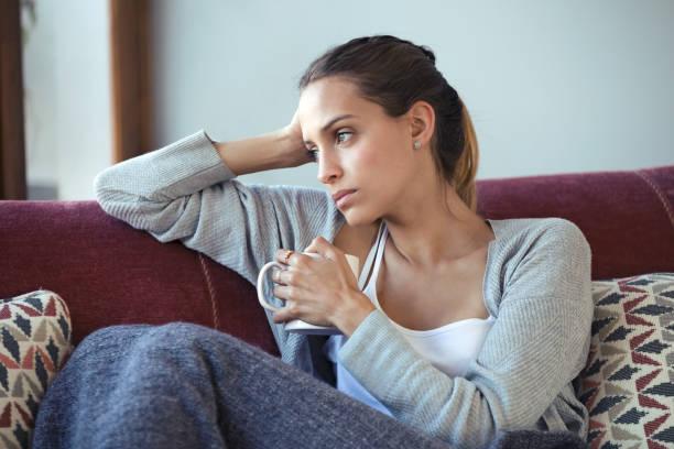 Depressive junge Frau, die über ihre Probleme nachdenkt, während sie zu Hause Kaffee auf dem Sofa trinkt. – Foto