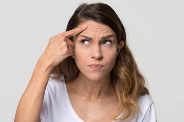 沮喪的年輕女子觸摸額頭擔心皮膚皺紋 - 弄皺的 個照片及圖片檔